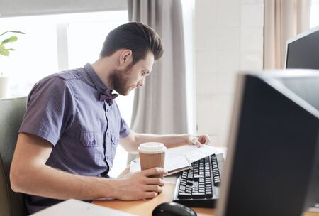 personas leyendo: business, startup and people concept - businessman or creative male office worker drinking coffee and reading papers Foto de archivo