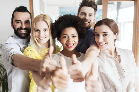 bedrijf, opstarten, mensen en teamwork concept - gelukkig creatieve team blijkt thumbs up in het kantoor