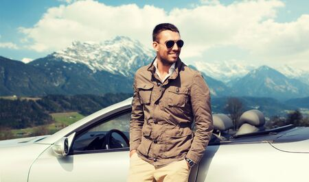 trip over: travel, tourism, road trip, transport and people concept - happy man near cabriolet car over mountains background