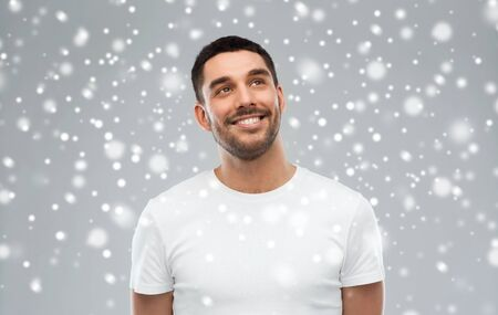 winter, christmas, idea, inspiration and people concept - happy smiling young man looking up over snow on gray background Stock Photo