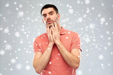 facial expression, winter, christmas and people concept - young man in polo t-shirt touching his face over snow on gray background