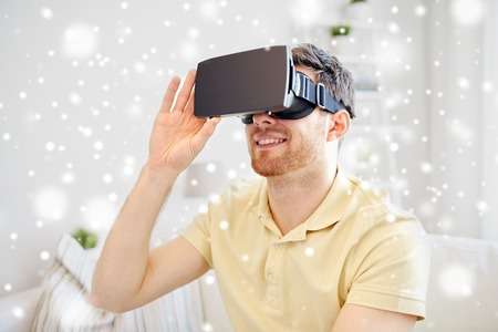 mediated: technology, augmented reality, gaming, entertainment and people concept - happy young man with virtual headset or 3d glasses playing video game over snow