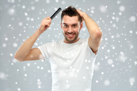 groomed: beauty, grooming, winter, christmas and people concept - smiling young man brushing hair with comb over snow on gray background Stock Photo