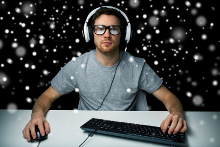 cyber terrorism: technology, gaming, lets play and people concept - man or hacker in headset and eyeglasses with pc computer playing game and streaming playthrough or walkthrough video over black background over snow Stock Photo