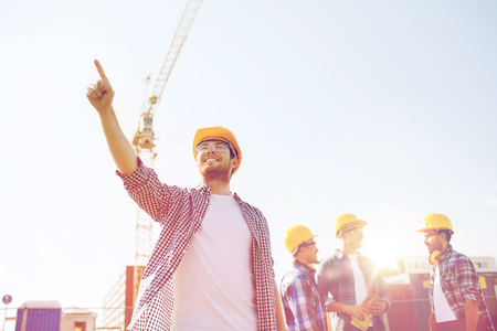 business, building, teamwork and people concept - group of smiling builders in hardhats pointing finger outdoors