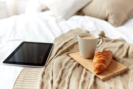 technology, coziness, morning and winter concept - tablet pc computer, coffee cup and croissant on bed at home