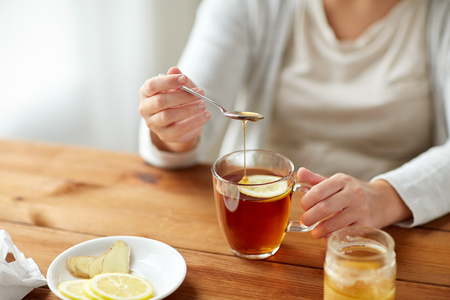 health, traditional medicine and ethnoscience concept - close up of ill woman drinking tea with lemon, honey and ginger at wooden table Imagens