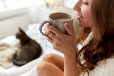 cosiness: winter, cosiness, leisure and people concept - close up of happy young woman with cup of coffee or cacao and cat in bed at home Stock Photo