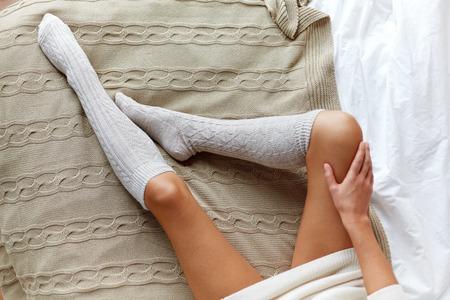 sexy füsse: Winter, Kleidung, Mode und Menschen Konzept - Nahaufnahme zu Hause der jungen Frau, die Beine in Kniestrümpfen im Bett
