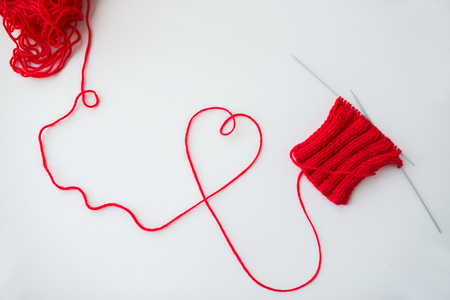 domestic life: handicraft, love, valentines day and needlework concept - hand-knitted item with knitting needles and thread in heart shape Stock Photo