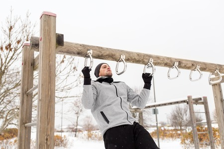 grapple: fitness, sport, exercising, training and people concept - young man doing pull ups on horizontal bar outdoors in winter