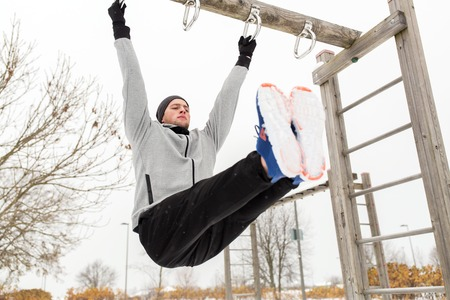 grapple: fitness, sport, exercising, training and people concept - young man doing leg pull ups on horizontal bar and flexing abdominal muscles outdoors in winter Stock Photo