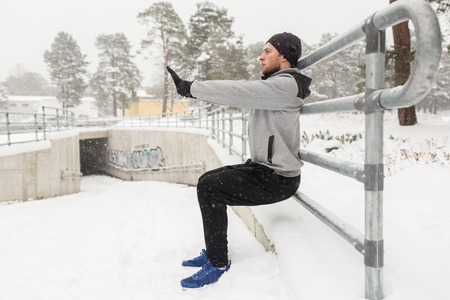fitness, sport, people, exercising and healthy lifestyle concept - young man doing squats and warmig up at fence in winter