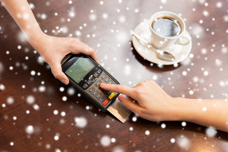 pin code: people, finance, payment, technology and consumerism concept - close up of waitress holding credit card reader and customer hand entering pin code at cafe over snow