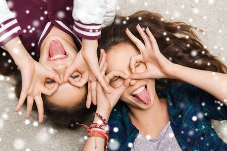 happy smiling: people, friends, winter, christmas and friendship concept - happy smiling pretty teenage girls having fun and making faces over snow Stock Photo