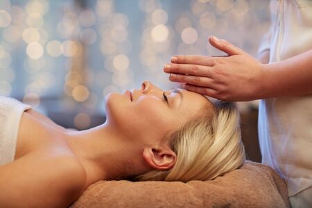 relaxation massage: people, beauty, spa, healthy lifestyle and relaxation concept - close up of beautiful young woman lying with closed eyes and having face or head massage in spa Stock Photo