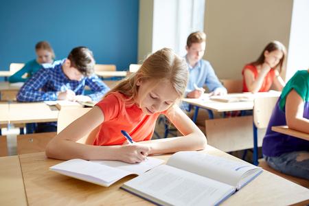 教育、学習、人々 の概念 - 学校のテストを書いて本に学生の女の子 写真素材 - 68094413