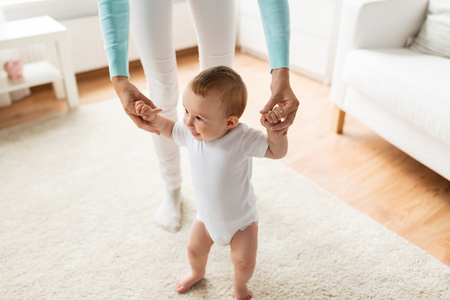 family, child, childhood and parenthood concept - happy little baby learning to walk with mother help at home Foto de archivo