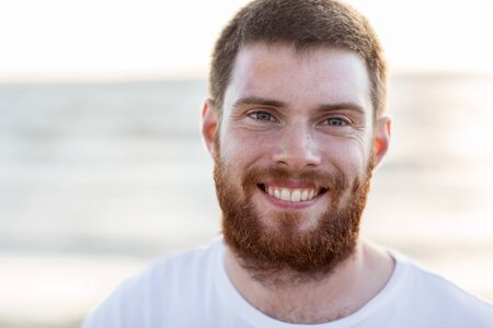 beard man: people, emotion and facial expression concept - face of happy smiling young man with red beard on beach