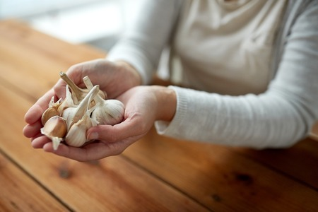indigenous medicine: health, people, food, traditional medicine and ethnoscience concept - woman hands holding garlic for cooking or healing