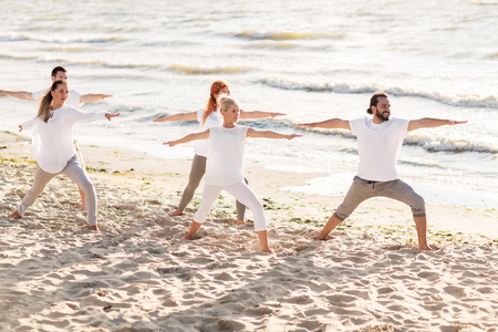 fitness, sport and healthy lifestyle concept - group of people making yoga in warrior pose on beach