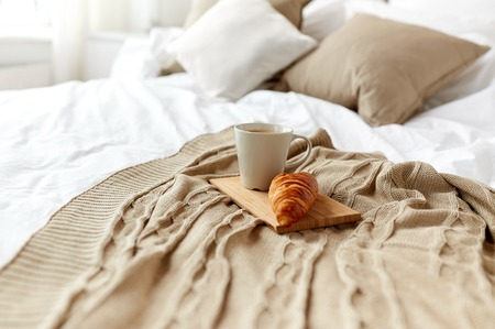 cosy: breakfast, coziness, morning, holidays and winter concept - cozy bedroom with coffee cup and croissant on wooden board in bed at home
