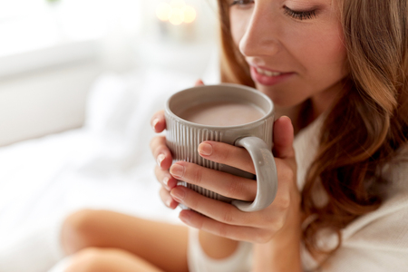 coziness: morning, coziness, winter and people concept - close up of happy young woman with cup of coffee or cocoa drink in bed at home