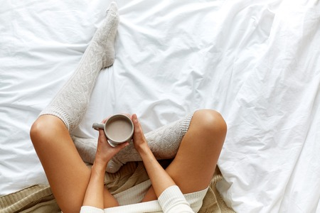 morning, coziness, winter and people concept - close up of young woman with cup of coffee or cacao in bed at home Stock Photo