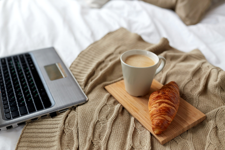 coziness: coziness, morning, technology and breakfast concept - bedroom with laptop computer, coffee cup and croissant on bed at home Stock Photo