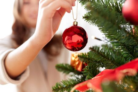 decorating: x-mas, winter holidays and people concept - happy young woman decorating christmas tree with ball at home Stock Photo
