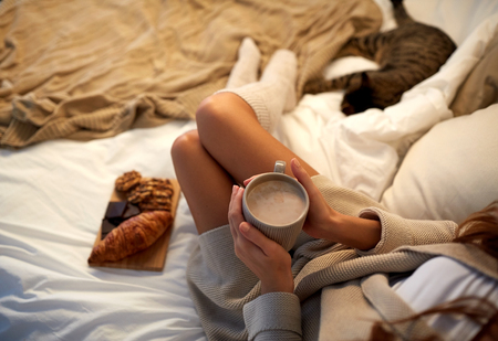 coziness: winter, coziness, leisure and people concept - close up of young woman with cup of coffee or cacao and sweets in bed at home