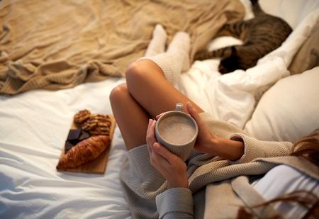 Winter, Gemütlichkeit, Freizeit und Menschen Konzept - Nahaufnahme zu Hause der jungen Frau mit einer Tasse Kaffee oder Kakao und Süßigkeiten im Bett