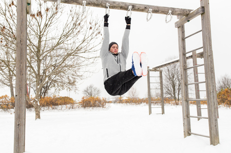 gym workout: fitness, sport, exercising, training and people concept - young man doing leg pull ups on horizontal bar and flexing abdominal muscles outdoors in winter Stock Photo