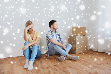 unhappy people: people, relationship difficulties, divorce, conflict and family concept - unhappy couple having argument or break up at home over snow Stock Photo