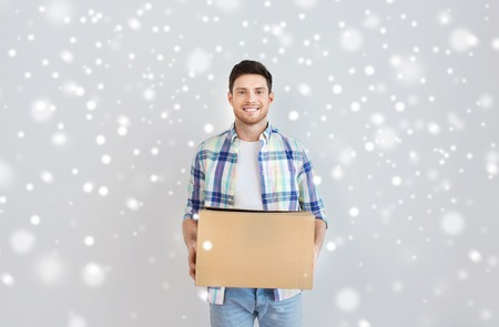 nice accommodations: moving, delivery, housing, accommodation and people concept - smiling young man with cardboard box at home over snow