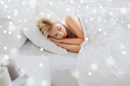 cosiness: rest, comfort, cosiness and people concept - young woman sleeping in bed at home bedroom over snow Stock Photo