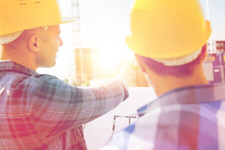people development: building, construction, development, teamwork and people concept - close up of builders with blueprint at building site