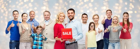happy shopping: shopping, family, generation and people concept - group of happy men and women showing thumbs up and sale sign over holidays lights background