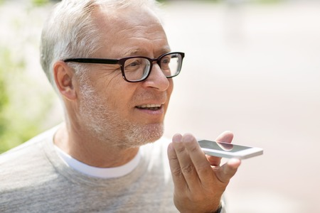 using voice: technology, senior people, lifestyle and communication concept - close up of happy old man using voice command recorder or calling on smartphone outdoors
