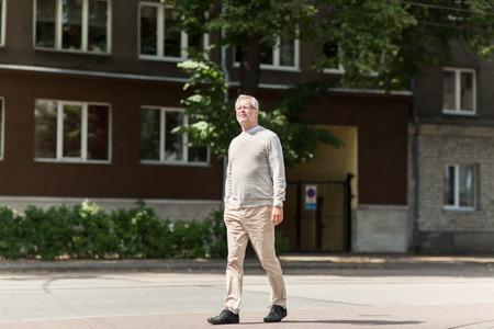 persona caminando: el ocio y el concepto de la gente - hombre mayor que recorre a lo largo del verano calle de la ciudad
