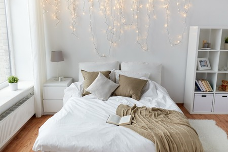 cosy: coziness, comfort, interior and holidays concept - cozy bedroom with bed and christmas garland lights at home Stock Photo