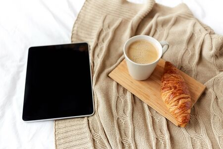 coziness: technology, coziness, morning and winter concept - tablet pc computer, coffee cup and croissant on bed at home