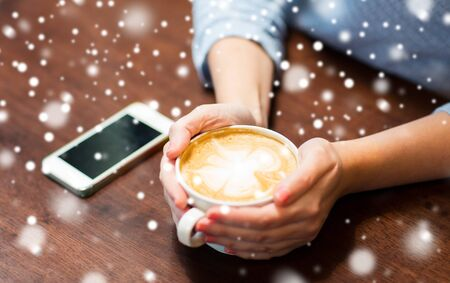 body parts cell phone: drinks, people, technology and lifestyle concept - close up of young woman with smartphone drinking coffee at cafe over snow Stock Photo