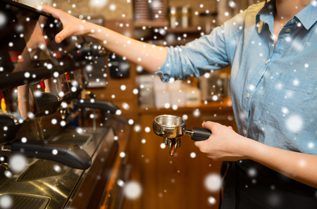 equipment, people and technology concept - close up of woman making coffee by machine at cafe bar or restaurant kitchen over snow Stock Photo