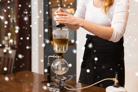 vac: equipment, people and technology concept - close up of woman with pot pouring ground coffee to siphon coffeemaker at cafe bar or restaurant kitchen over snow Stock Photo