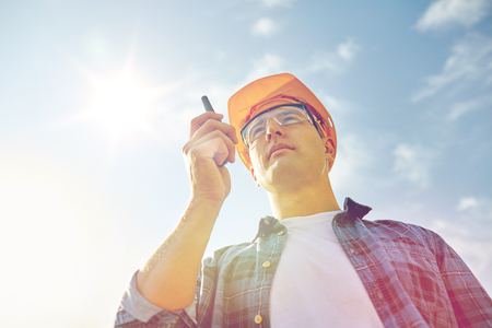 walkie talkie: industry, building, technology and people concept - close up of male builder in hardhat with walkie talkie or radio outdoors Stock Photo