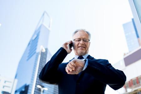 puntualidad: negocios, tecnología, tiempo, la puntualidad y el concepto de la gente - hombre de negocios mayor que invita al teléfono inteligente un mira el reloj en la ciudad
