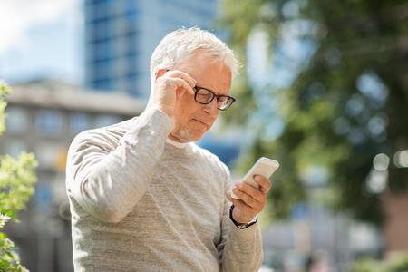 technologie, mensen, levensstijl en communicatie concept - senior man SMS-bericht op smartphone in de stad