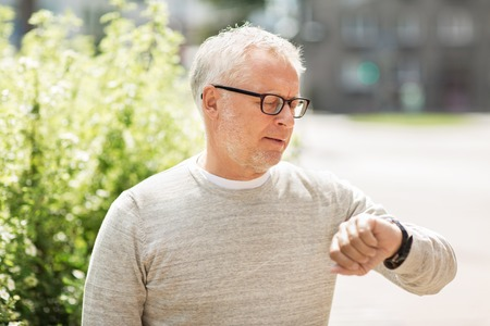 punctuality: punctuality and people concept - senior man checking time on his wristwatch or smartwatch in city