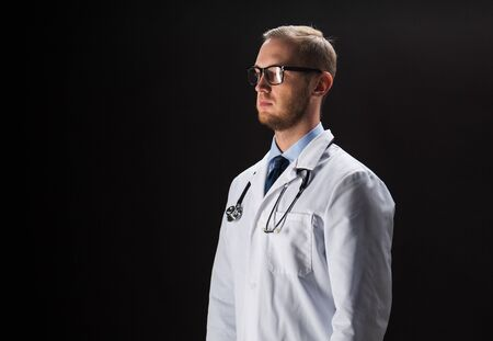 white coat: healthcare, people, profession and medicine concept - male doctor in white coat with stethoscope over black background